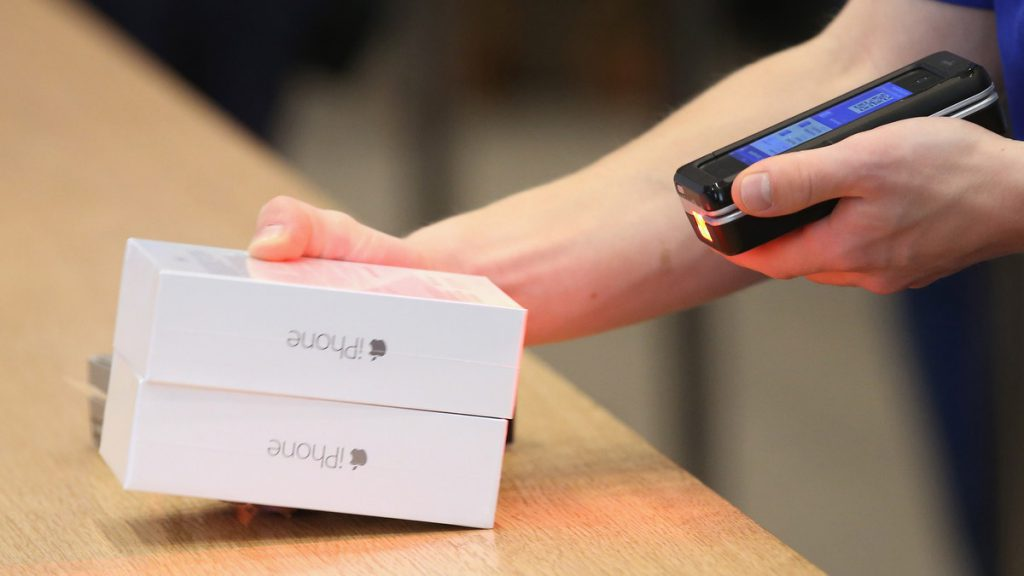 BERLIN, GERMANY - SEPTEMBER 19: A sales assistant scans new Apple iPhone 6 phones at the Apple Store on the first day of sales of the new phone in Germany on September 19, 2014 in Berlin, Germany. Hundreds of people had waited in a line that went around the block through the night in order to be among the first people to buy the new smartphone, which comes in two versions: the Apple iPhone 6 and the somewhat larger Apple iPhone 6 Plus. Sean Gallup/Getty Images